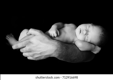 Dad holding his newborn baby in his hand. Baby lying on his father's arm. Father caring for his baby.