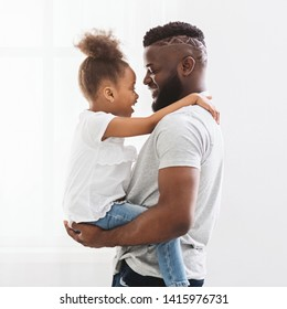 Dad hugging his little daughter, holding her on hands at home, side view