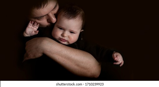 Dad hugging and kissing his baby on the black background. Love and care of father for baby concept.