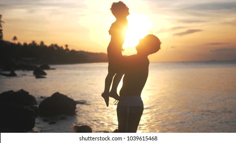 Dad keeps on his hands and throws son at amazing sunset on tropical beach. Happy travel concept