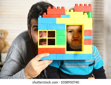 Dad and kid hide behind building wall made of blocks. Family game and childhood concept. Boy man play on defocused background. Father and son make grimaces looking through window of toy construction