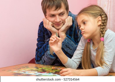 Dad with a kind smile looking at her daughter who is considering an element of the puzzle thinking where to put it