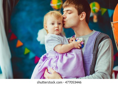 Dad kisses head of his little daughter while they stand before a window