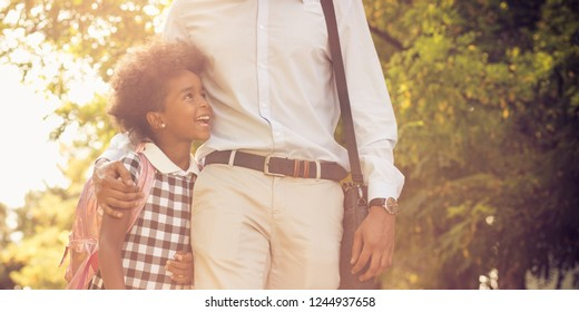 Dad knows how to smile. African American father and his daughter walking trough park. Close up.