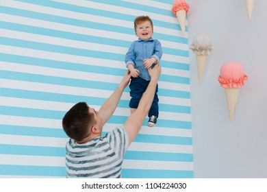 Dad lifting his baby up. Fooling around in colorfull babyroom decorated with icecream