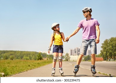 Dad with little daughter on the skates. two people rollerblade. sports family rollerskating outdoor