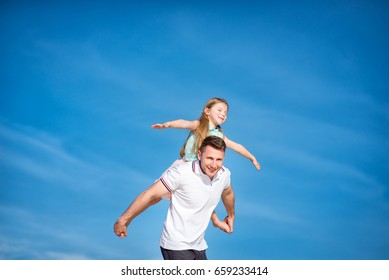 Dad and little girl daughter playing on the beach, fly, run, laugh at the blue sky background