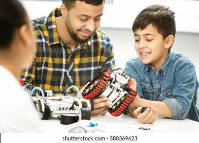 Dad, look! Cheerful father smiling playing with his son family building robots together bonding activity education technology vehicle toys playtime enjoyment care love parents mom dad children concept