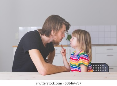 dad looking angry arguing with his daughter in preschool age sitting on kitchen at home