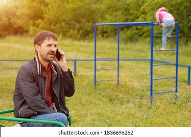 Dad looks at his phone and does not follow children in the playground