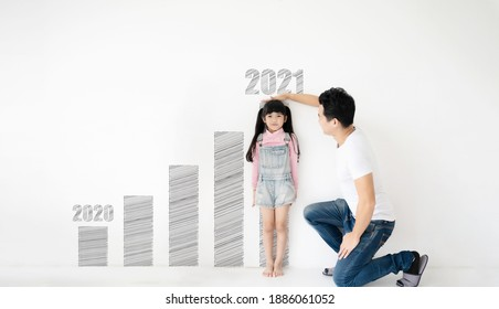 Dad measures height increase of her child daughter at white brick wall with graph growing growth year 2020 to 2021