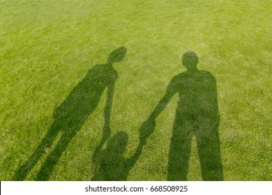Dad mom and baby - Shadow of a happy family on green lawn