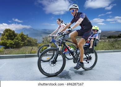 Dad, mom, a child on a bike ride