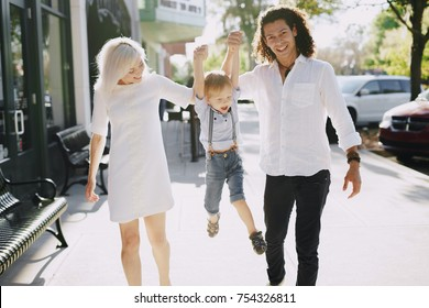 dad mom and a little boy with blond hair walking around the city and enjoying the sunshine, multi family black and white