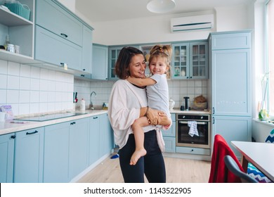 dad, mom, little daughter in the kitchen. Mom holds her daughter in her arms