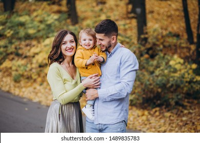 Dad mom and little son are walking in the autumn forest. Falling yellow leaves.Family running, having fun and playing with the baby.