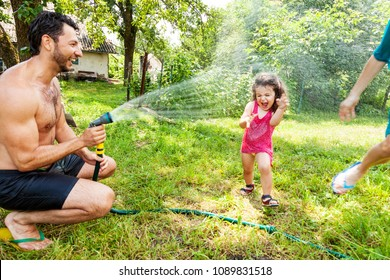 Dad and mom play with a little daughter outdoors in the summer, pouring water from a hose