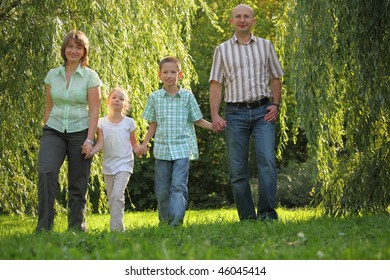 dad, mom, son and daughter is walking in early fall park.
