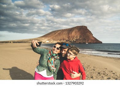 Dad mom with son taking selfie smiling and happy at the beach near the ocean. Parents with child on holiday making pictures for memories of an exotic vacation. Family portrait mountain sea cloudy sky
