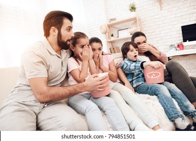 Dad, mom, two girls and a boy watch movies on TV. They are sitting on the couch in their apartment. They eat popcorn. They are a happy family.