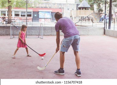dad playing floor ball with kid. field hockey game at children playground. active free time with kids.