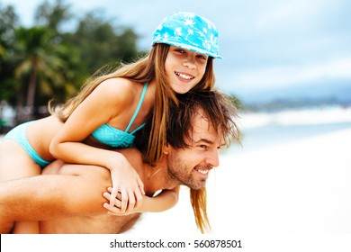 Dad playing with his 10 years old daughter on the tropical beach.