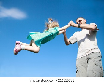 Dad playing with his baby daughter in a blue dress, he turns her around himself at arm's length, selective focus, the effect of motion