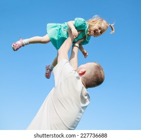Dad playing with his baby daughter in a blue dress, throws her over his head, selective focus