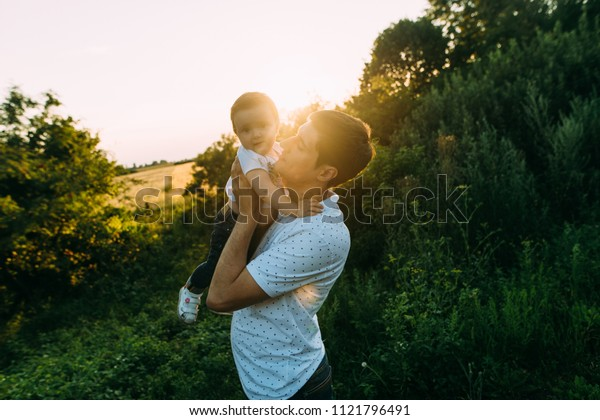 Dad playing with his child in the field, during the sunset.