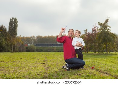 Dad playing with son throwing a paper airplane