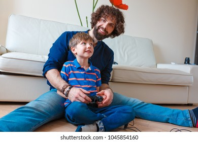 Dad playing video games with excited son bonding laughing sitting on floor at home, happy boy and young man having fun holding controllers, family gamers enjoying console on leisure, fathers day