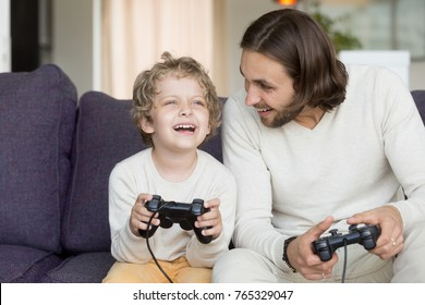 Dad playing video games with excited son bonding laughing sitting on couch at home, happy boy and young man having fun holding controllers, family gamers enjoying console on leisure, fathers day