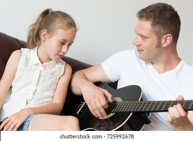 Dad plays the guitar for his daughter.