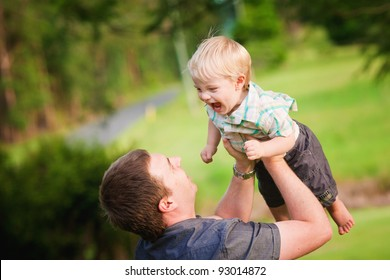 A Dad plays with his little boy in the outdoors in summer.