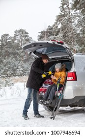 Dad pouring hot tea for girl after sports activities such as ski. Sitting in trunk of suv with opened back door at winter season