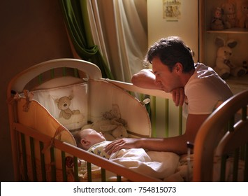 Dad puts his son to bed. before bedtime. dream. a lullaby of songs. Portrait of a father with his son. Child in the crib.