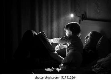 Dad is reading a bedtime story to his little son. Night lamp is shine beautifully. Black and white image with selective focus.