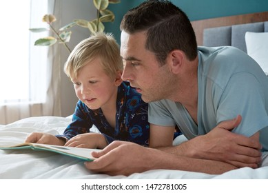 dad reading a storybook with his son, childhood bonding close relationship love tender moment