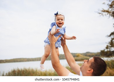 Dad rises up his hands with a little girl standing before the lake