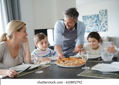 Dad serving pizza to family at dining table