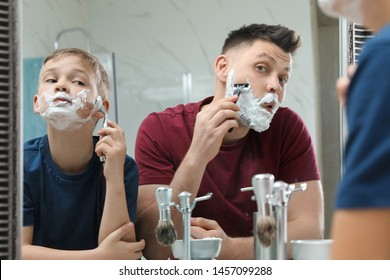 Dad shaving and son imitating him at mirror in bathroom
