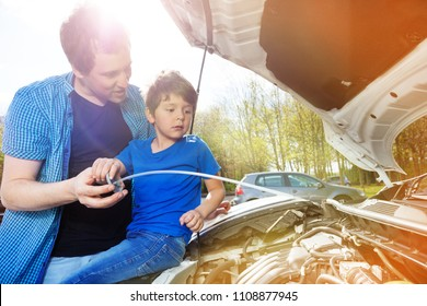 Dad showing his son oil level in car engine