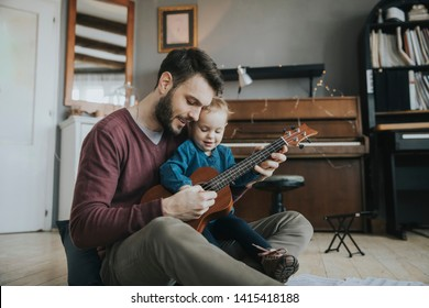 Dad shows the girl how to play the guitar in the room