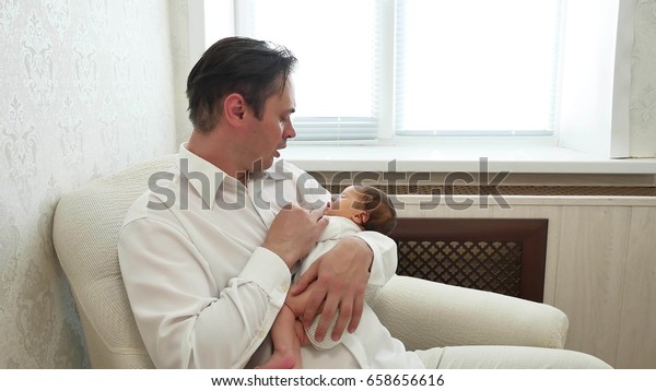 dad sings lullaby child, baby is sleeping on dad hands