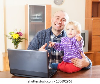 dad sitting at  laptop with  young daughter on his lap
