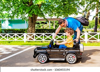 Dad and son in the amusement park. Dad teaches son to drive a car on a sunny summer day