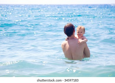 dad and son bathing together in the sea