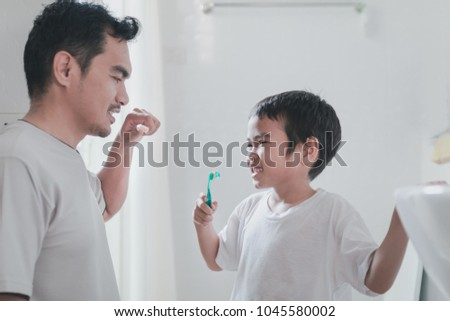 Dad And Son Are Brushing Their Teeth Together In The Morning