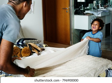 Dad and son changing bed sheet together