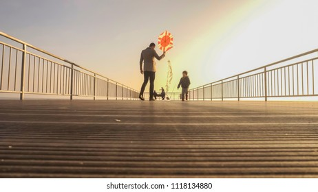 Dad and son child are flying a kite together in summer. Happy family in summer nature. Dad enjoying time with his kid outdoor. Family relationship and love concept. Sunset colors and vintage filter.